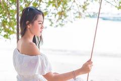 Mujer asiática en el vestido blanco que se sienta en el oscilación en la playa Gente y Foto de archivo libre de regalías