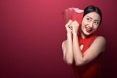Mujer asiática en el vestido del cheongsam que sostiene angpao fotos de archivo libres de regalías