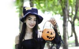Mujer asiática en el vestido negro y sostener la muñeca plástica de la calabaza fotografía de archivo