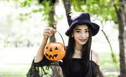 Mujer asiática en el vestido negro y sostener la muñeca plástica de la calabaza fotografía de archivo libre de regalías