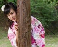 Mujer asiática en kimono detrás del pilar de madera Imagen de archivo