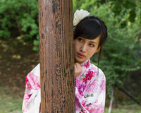 Mujer asiática en kimono detrás del pilar de madera Imagenes de archivo