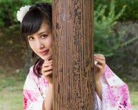 Mujer asiática en kimono detrás del pilar de madera Foto de archivo