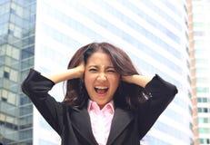 Mujer asiática en la habitación del negocio con la cara enojada imagen de archivo