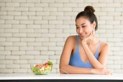 Mujer asiática en posturas alegres con el cuenco de ensalada en el lado fotos de archivo
