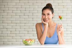 Mujer asiática en posturas alegres con el cuenco de ensalada en el lado foto de archivo libre de regalías