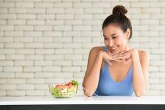 Mujer asiática en posturas alegres con el cuenco de ensalada en el lado imagenes de archivo
