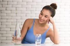 Mujer asiática en posturas alegres con la botella y el vidrio de agua potable en el lado imagen de archivo libre de regalías
