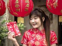 Mujer asiática en un festival del traje que sostiene un bolsillo rojo - dinero afortunado Día de fiesta de Tet Año Nuevo chino foto de archivo