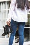 Mujer asiática en vaqueros con la camiseta blanca que sostiene los zapatos negros del talón imagen de archivo libre de regalías