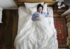 Mujer asiática enferma con fiebre que duerme en la cama imagenes de archivo