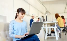 Mujer asiática feliz con el ordenador portátil que trabaja en la oficina fotos de archivo