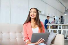 Mujer asiática feliz con la PC de la tableta que trabaja en la oficina imagenes de archivo