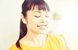 Mujer asiática feliz con música que escucha de los auriculares Imagenes de archivo