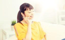 Mujer asiática feliz con música que escucha de los auriculares Fotografía de archivo
