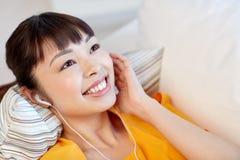 Mujer asiática feliz con música que escucha de los auriculares Imagen de archivo libre de regalías