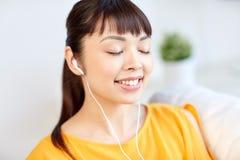 Mujer asiática feliz con música que escucha de los auriculares Imágenes de archivo libres de regalías