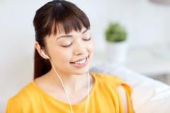 Mujer asiática feliz con música que escucha de los auriculares Fotos de archivo