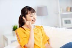 Mujer asiática feliz con música que escucha de los auriculares Fotografía de archivo libre de regalías