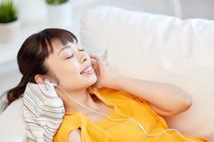 Mujer asiática feliz con música que escucha de los auriculares Foto de archivo