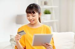 Mujer asiática feliz con PC de la tableta y la tarjeta de crédito Imágenes de archivo libres de regalías