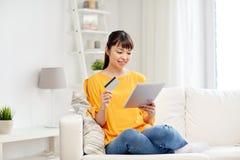 Mujer asiática feliz con PC de la tableta y la tarjeta de crédito Fotos de archivo libres de regalías