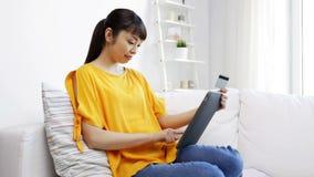 Mujer asiática feliz con PC de la tableta y la tarjeta de crédito almacen de metraje de vídeo