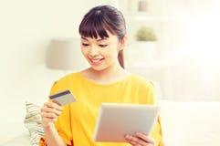Mujer asiática feliz con PC de la tableta y la tarjeta de crédito Foto de archivo