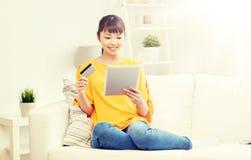 Mujer asiática feliz con PC de la tableta y la tarjeta de crédito Imagenes de archivo