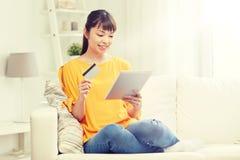 Mujer asiática feliz con PC de la tableta y la tarjeta de crédito Imagen de archivo libre de regalías