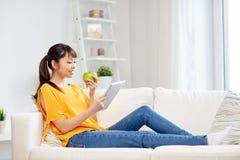 Mujer asiática feliz con PC y la manzana de la tableta en casa Foto de archivo libre de regalías