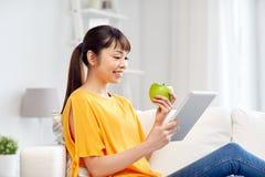 Mujer asiática feliz con PC y la manzana de la tableta en casa Fotografía de archivo libre de regalías