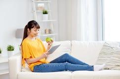 Mujer asiática feliz con PC y la manzana de la tableta en casa Imagen de archivo