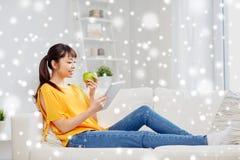 Mujer asiática feliz con PC y la manzana de la tableta en casa Imagenes de archivo