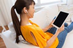 Mujer asiática feliz con PC y los auriculares de la tableta Fotografía de archivo