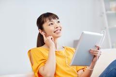Mujer asiática feliz con PC y los auriculares de la tableta Fotografía de archivo libre de regalías