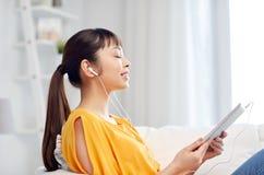 Mujer asiática feliz con PC y los auriculares de la tableta Imagen de archivo