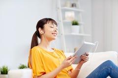 Mujer asiática feliz con PC y los auriculares de la tableta Fotos de archivo