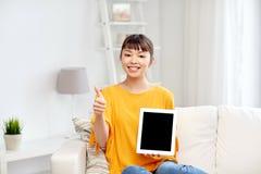 Mujer asiática feliz con PC y los pulgares de la tableta para arriba Imagen de archivo