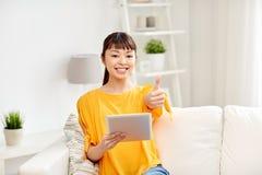 Mujer asiática feliz con PC y los pulgares de la tableta para arriba Imagenes de archivo