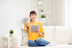 Mujer asiática feliz con PC y los pulgares de la tableta para arriba Foto de archivo