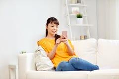 Mujer asiática feliz con smartphone en casa Fotografía de archivo libre de regalías