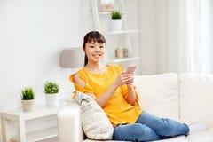 Mujer asiática feliz con smartphone en casa Foto de archivo