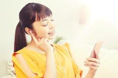 Mujer asiática feliz con smartphone y los auriculares Imagenes de archivo