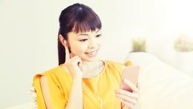 Mujer asiática feliz con smartphone y los auriculares Fotos de archivo libres de regalías