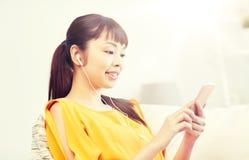 Mujer asiática feliz con smartphone y los auriculares Fotografía de archivo libre de regalías
