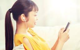 Mujer asiática feliz con smartphone y los auriculares Foto de archivo libre de regalías