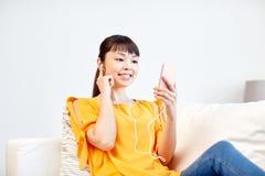 Mujer asiática feliz con smartphone y los auriculares Imagen de archivo libre de regalías