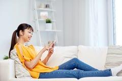 Mujer asiática feliz con smartphone y los auriculares Imágenes de archivo libres de regalías