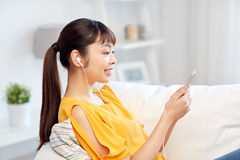 Mujer asiática feliz con smartphone y los auriculares Fotografía de archivo